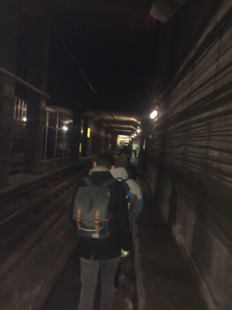 Photo shows a dark Metro tunnel and passengers in it