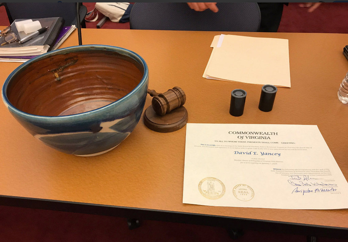 The certificate of election naming David Yancey the winner in 94th District House race on Thursday, Jan. 4, 2018 almost two months after the November election. A blue stoneware vessel created by Virginia artisit Stephen Glass was used for the drawing along with two new film canisters. (WTOP/Max Smith)