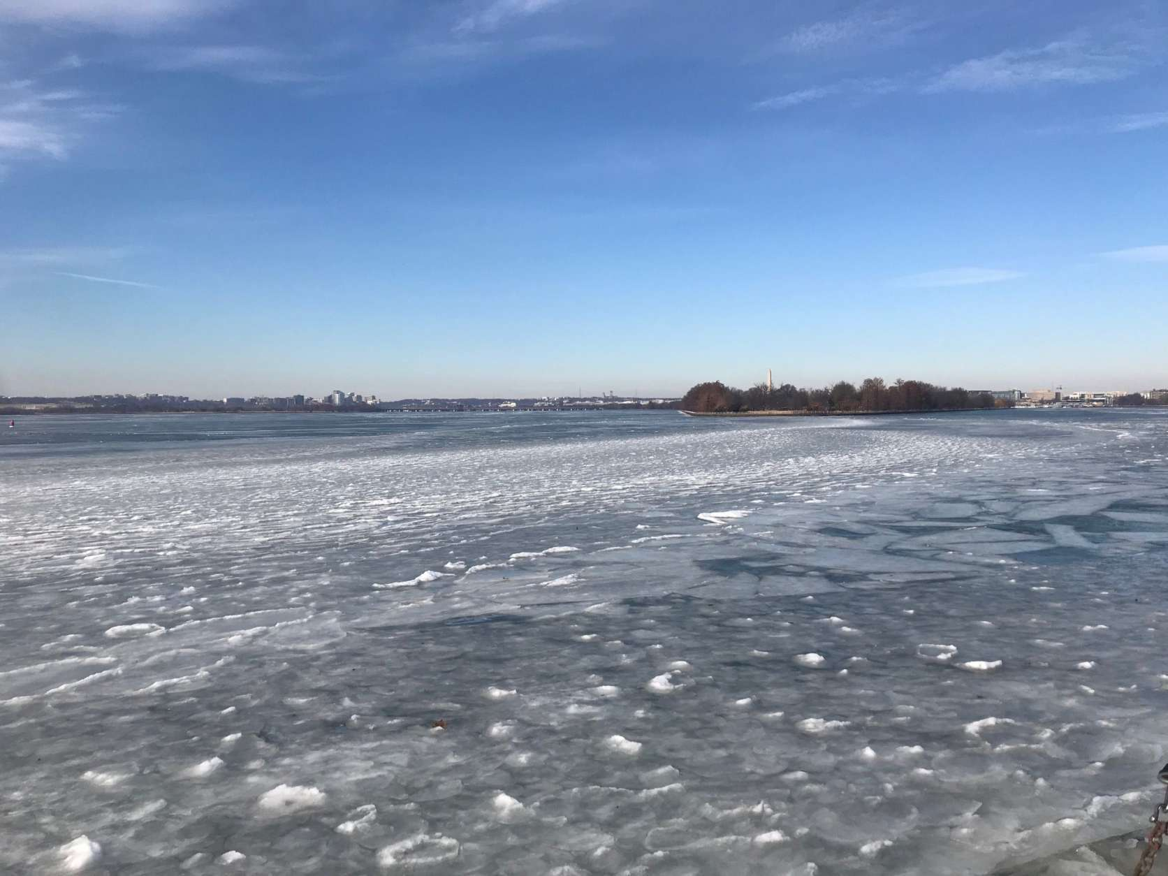 The layers of ice almost resemble waves hitting a shoreline, where the Anacostia and Potomac Rivers meet the Washington Channel. On the left is Arlington, Virginia and on the right Washington, DC. (WTOP/Megan Cloherty)