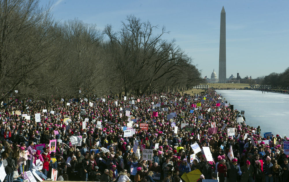 The Capitol and Washington Monument are seen as Women's March demonstrators line the Reflecting Pool at the Lincoln Memorial in Washington, Saturday, Jan. 20, 2018.  Activists are returning to the streets a year after millions of people rallied worldwide at marches for female empowerment, hoping to create an enduring political movement that will elect more women to government office.  (AP Photo/Cliff Owen)