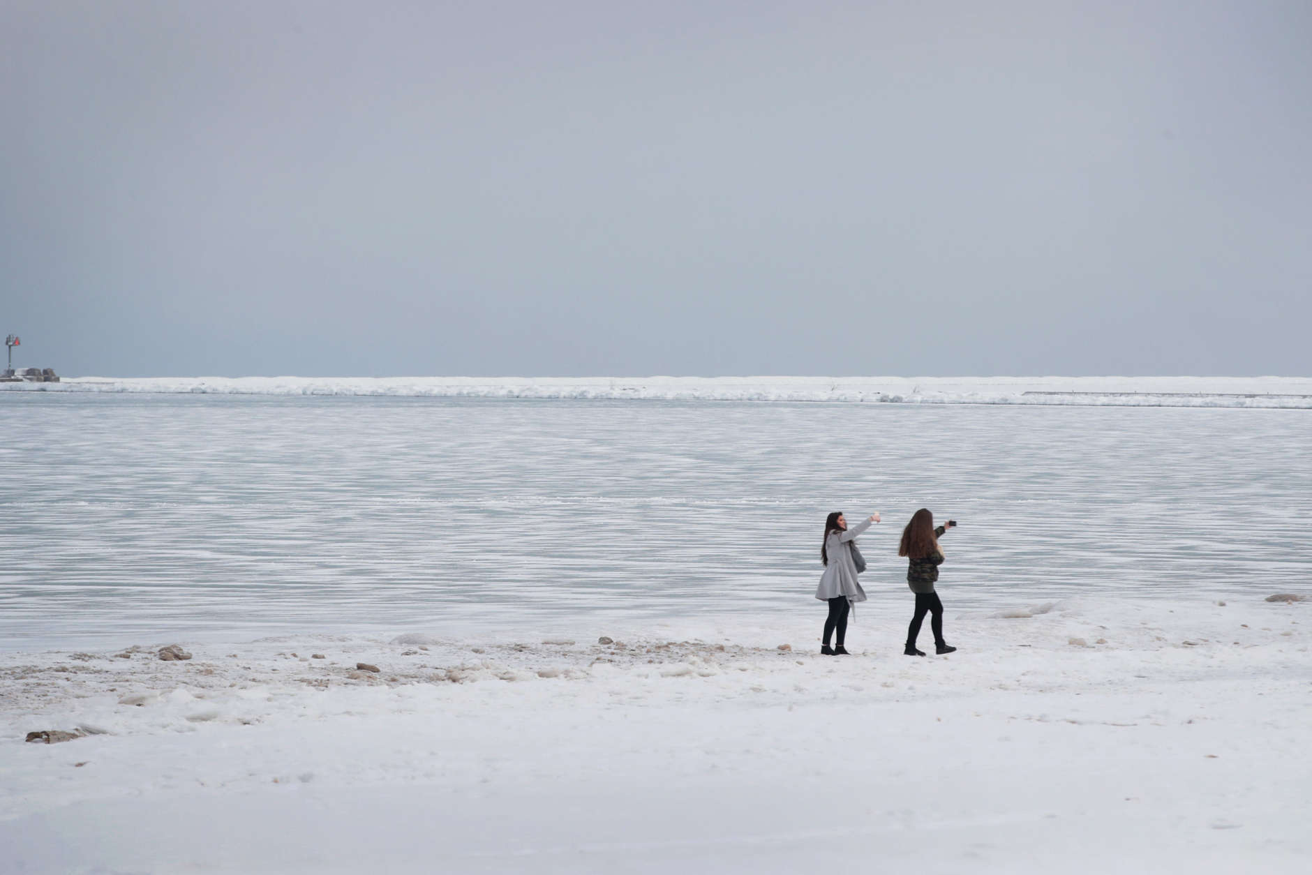 CHICAGO, IL - JANUARY 03: Visitors take selfies along the frozen shore of Lake Michigan on January 3, 2018 in Chicago, Illinois. Record cold temperatures are gripping much of the U.S. and are being blamed on several deaths over the past week.  (Photo by Scott Olson/Getty Images)