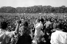 """FILE - In this Jan. 15, 1967 file photo, Timothy Leary, center, leads thousands in a song at the """"Human Be-In"""" on the Golden Gate Park Polo Fields in San Francisco. Dennis McNally, who has curated an exhibit at the California Historical Society, says the national media paid little attention to San Francisco's psychedelic community until January 1967, when poets and bands joined forces for the """"Human Be-In,"""" which unexpectedly drew about 50,000 people. Leary stood on stage and delivered his famous mantra: """"Turn on. Tune In. Drop out."""" (AP Photo)"""