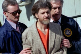 FILE - In this April 4, 1996 file photo, Ted Kaczynski, better known as the Unabomber, is flanked by federal agents as he is led to a car from the federal courthouse in Helena, Mont. Twenty years after the arrest of Kaczynski, some Lincoln residents remember him as an odd recluse who ate rabbits and lived without electricity, while others say he had a funny, personable side. Kaczynski is serving a life sentence in a federal prison in Florence, Colorado, for a series of bombings, most through the mail, that killed three people and injured 23 others over 17 years. (AP Photo/John Youngbear, File)