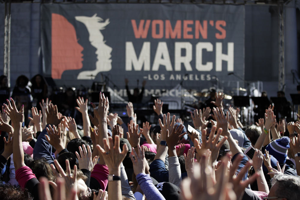 People hold their hands up at a Women's March against sexual violence and the policies of the Trump administration Saturday, Jan. 20, 2018, in Los Angeles. (AP Photo/Jae C. Hong)