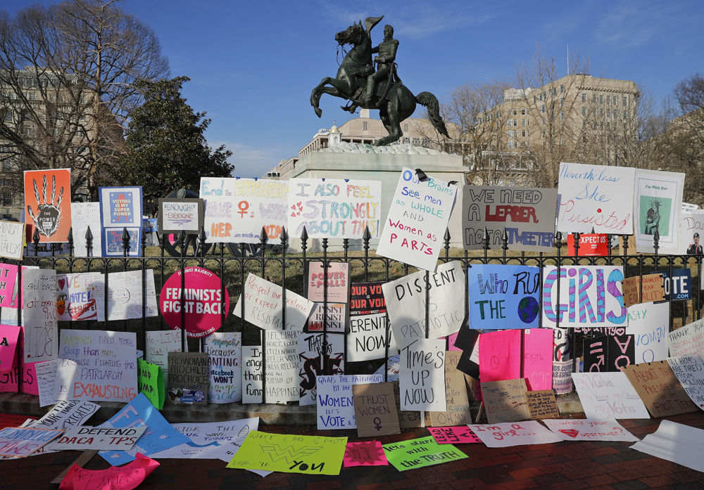 Signs are left at the base of statue of President Andrew Jackson in Lafayette Square, across the street from the White House in Washington, near the end of the Women's March demonstrators Saturday, Jan. 20, 2018. On the anniversary of President Donald Trump's inauguration, people participating in rallies and marches in the U.S. and around the world Saturday denounced his views on immigration, abortion, LGBT rights, women's rights and more. (AP Photo/Pablo Martinez Monsivais)