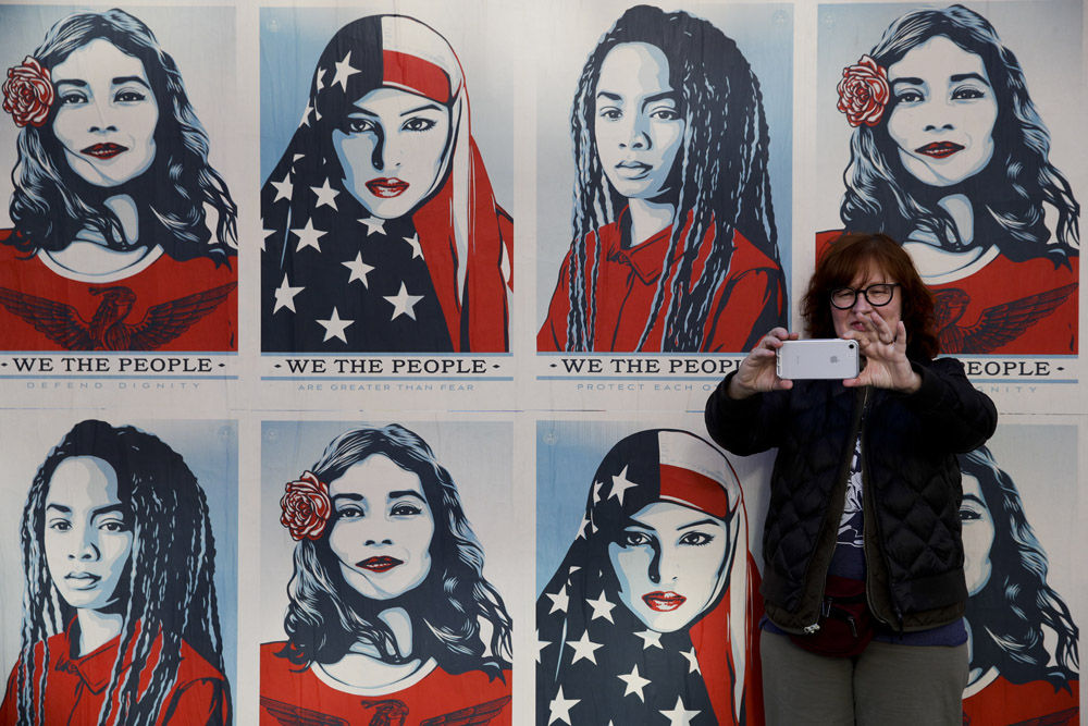 A protester takes a selfie in front of posters supporting women's rights during a Women's March, Saturday, Jan. 20, 2018, in Los Angeles. (AP Photo/Jae C. Hong)
