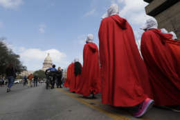 """Members of the """"Texas Handmaids"""" lead a women's march to the Texas State Capitol on the one-year anniversary of President Donald Trump's inauguration, Saturday, Jan. 20, 2018, in Austin, Texas. (AP Photo/Eric Gay)"""
