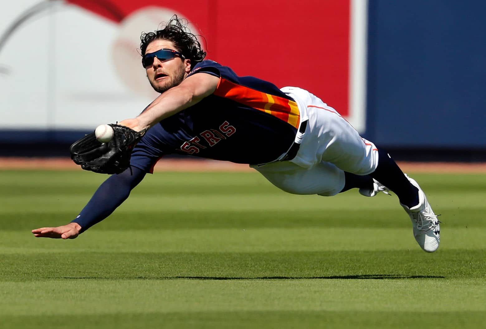 Houston Astros center fielder Jake Marisnick dives and catches a ball hit by Washington Nationals' Matt Adams to end the top of the first inning of an exhibition spring baseball game Friday.  (AP Photo/Jeff Roberson)