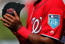 A member of the Washington Nationals holds his cap as Marjory Stoneman Douglas High School student Angelique Meneses sings the national anthem before the start of an exhibition spring baseball game against the Houston Astros, Friday, Feb. 23, 2018, in West Palm Beach, Fla. Players around the league are wearing the caps of the Marjory Stoneman Douglas High School Eagles baseball team to honor the victims of a shooting at the school last week. (AP Photo/Jeff Roberson)