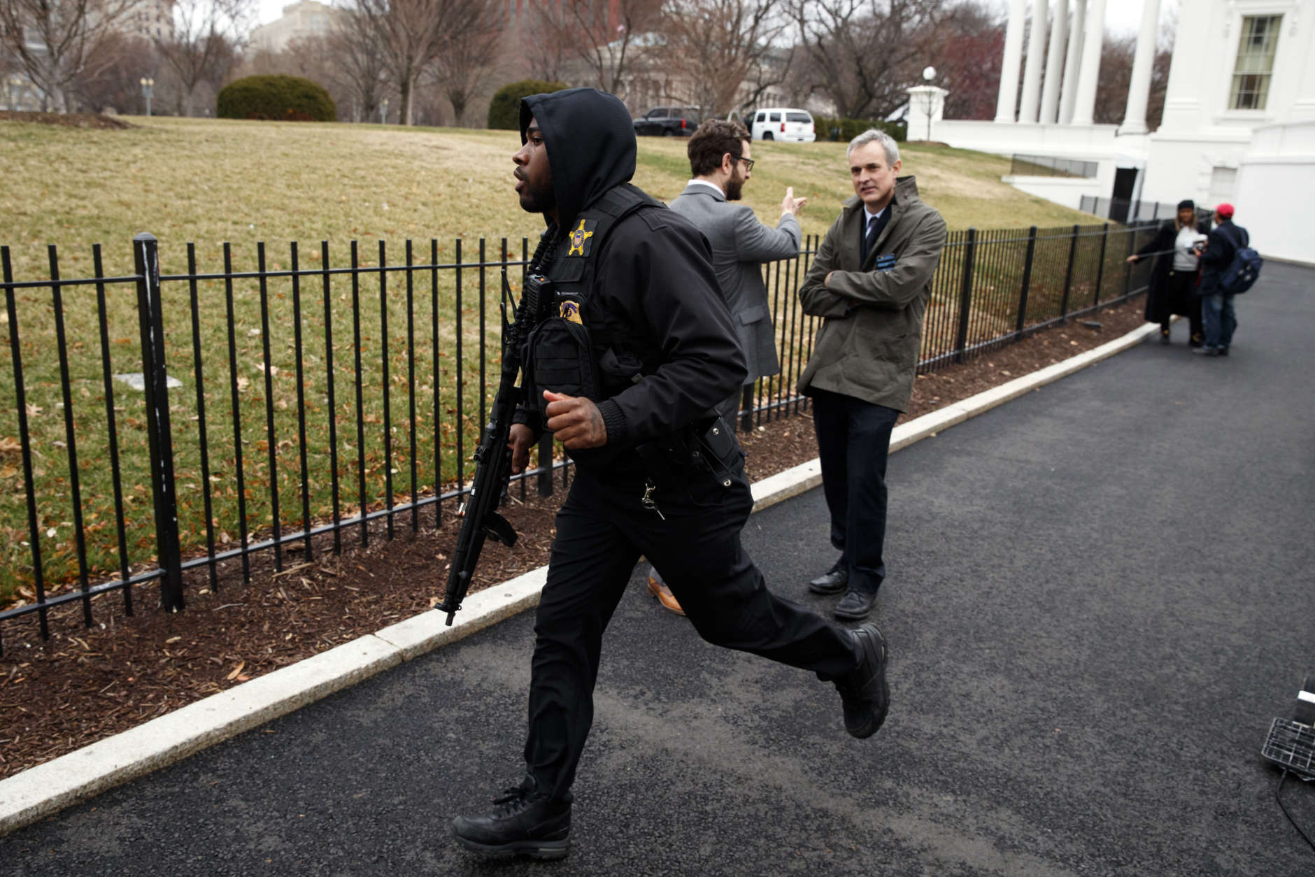 A Secret Service officer rushes past reporters after a vehicle rammed a barrier near the White House, Friday, Feb. 23, 2018, in Washington. (AP Photo/Evan Vucci)