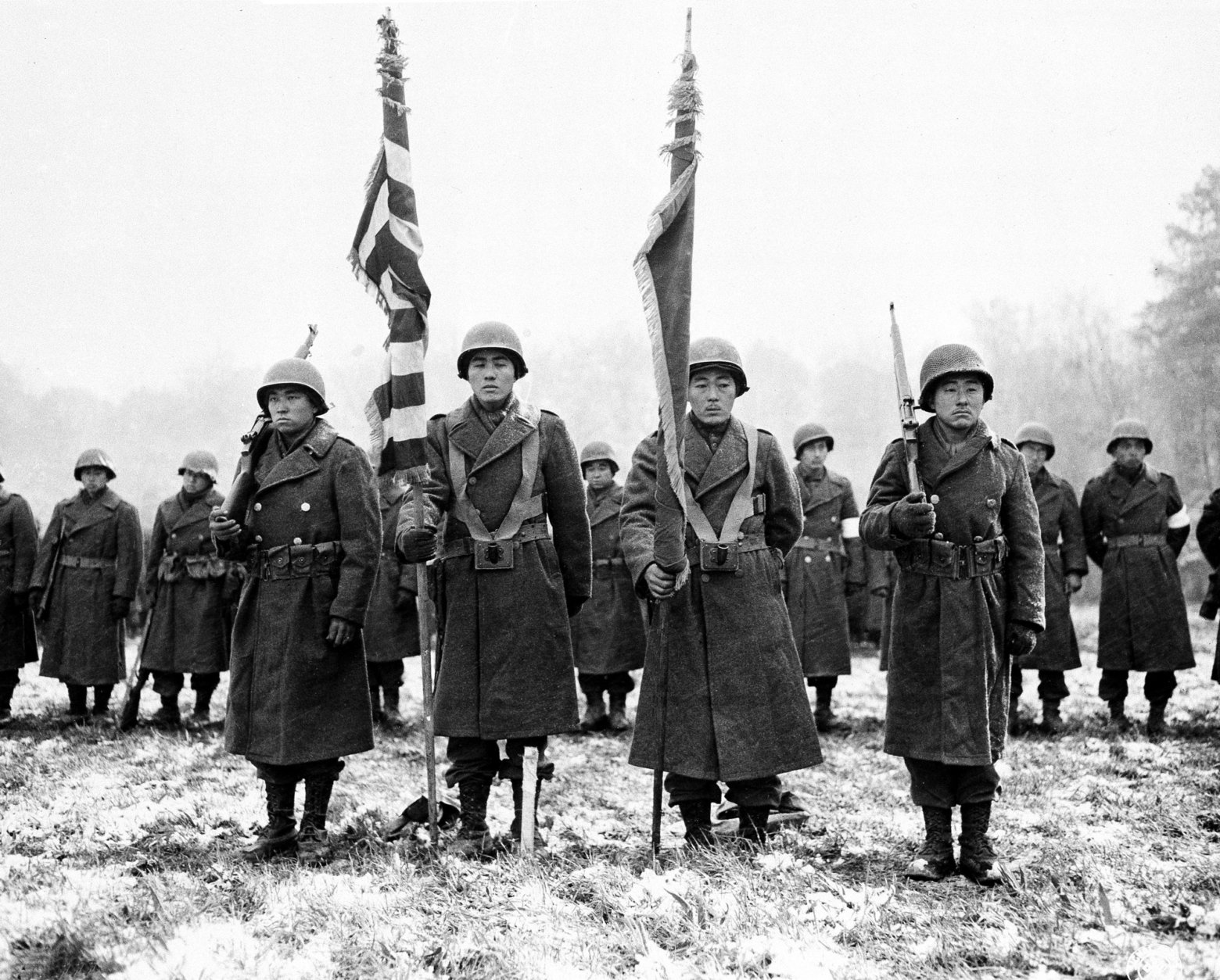 Two color guards and color bearers of the Japanese-American 442nd Combat team stand at attention while their citations are read somewhere in France during World War II on Nov. 12, 1944 .  They  are standing on the ground where many of their comrades fell.  (AP Photo/U.S. Army Signal Corps)