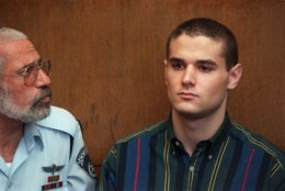 An Israeli police officer looks at Samuel Sheinbein at the Tel Aviv court Thursday, Sept. 2, 1999.  The Maryland teen-ager admitted in an Israeli court Thursday that he strangled an acquaintance in 1997, part of a plea bargain under which he will serve 24 years in an Israeli prison.   (AP Photo/Eyal Warshavsky)