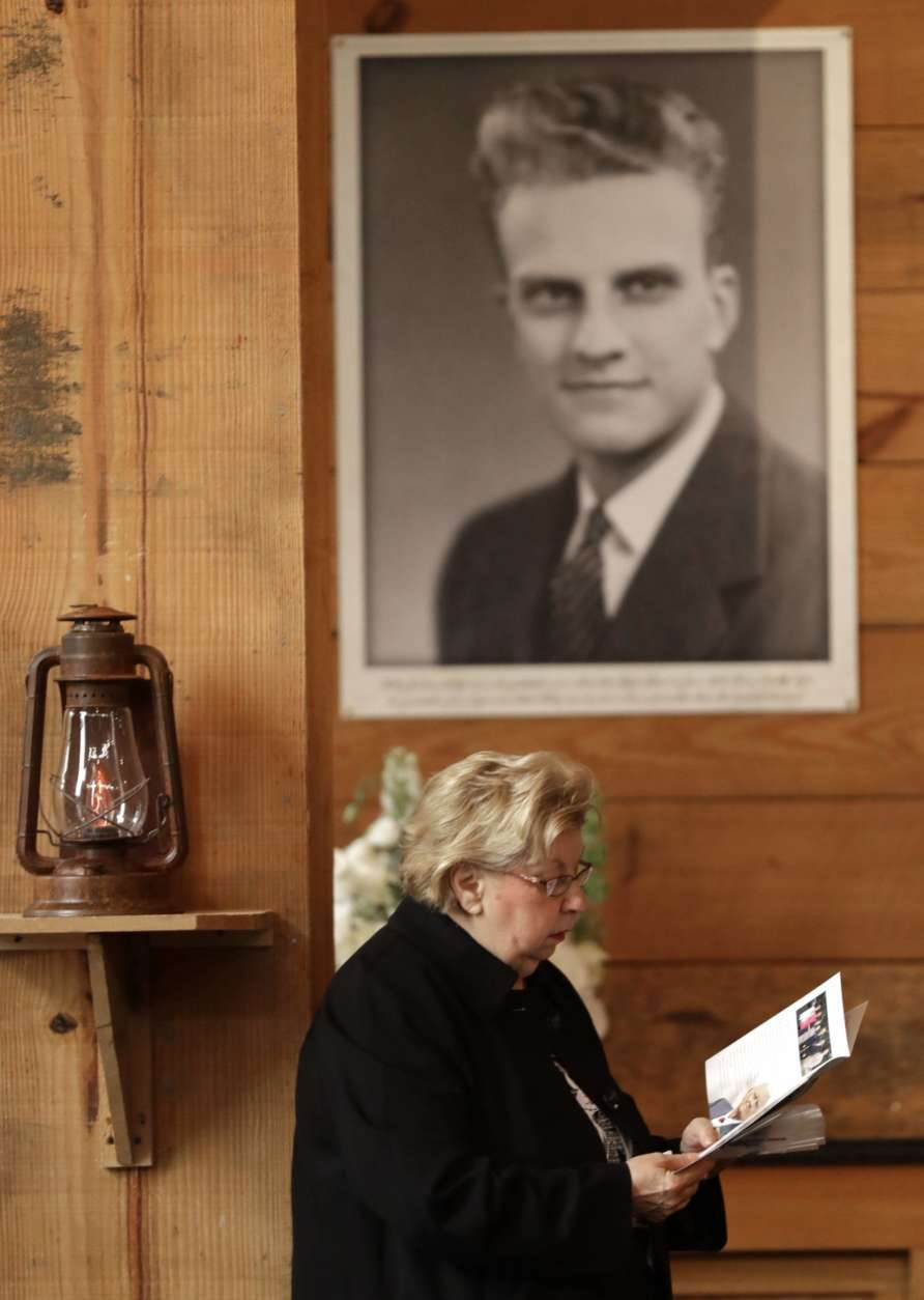 A woman reads a brochure under a large photo of Billy Graham as she pays respects to Billy Graham during a public viewing at the Billy Graham Library in Charlotte, N.C., Monday, Feb. 26, 2018. (AP Photo/Chuck Burton)