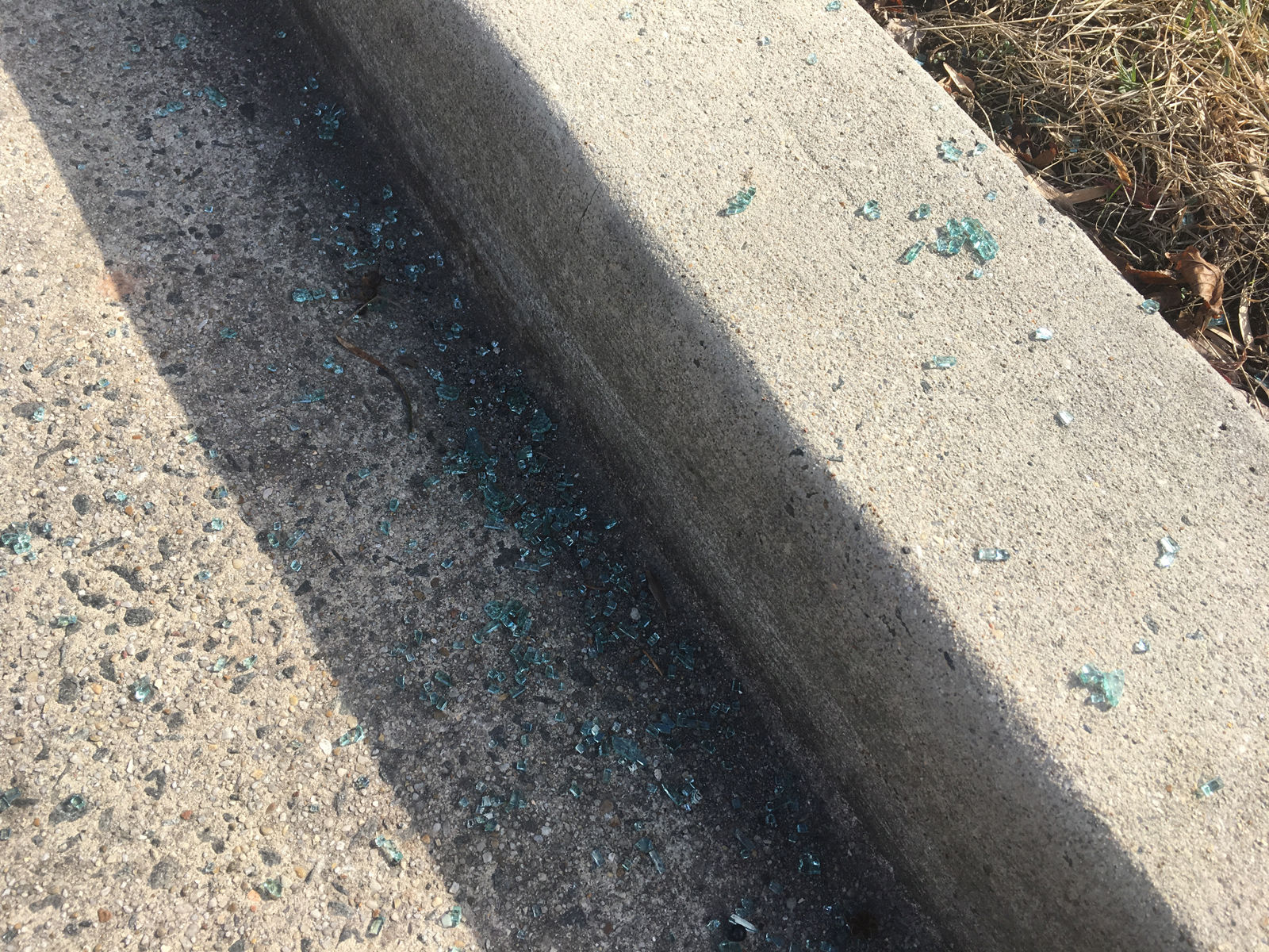 Glass on the ground in the Sheppard Park neighborhood of D.C. following a night when D.C. police said 47 cars were broken into. (WTOP/Mike Murillo)