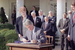 Pres. Clinton signs the Family Leave Bill as Vicki Yandle of Marietta, Ga., looks on in the Rose Garden of the White House, Feb. 5, 1993.  Mrs. Yandle lost her job when she took time off when her daughter was sick.  Behind the president, from left, are: House Speaker Thomas Foley, Sen. Edward M. Kennedy (D-Mass.), Rep. William Ford (D-Mich.), and Sen. Christopher Dodd (D-Conn.) At far right is Vice President Al Gore. (AP Photo/Greg Gibson)