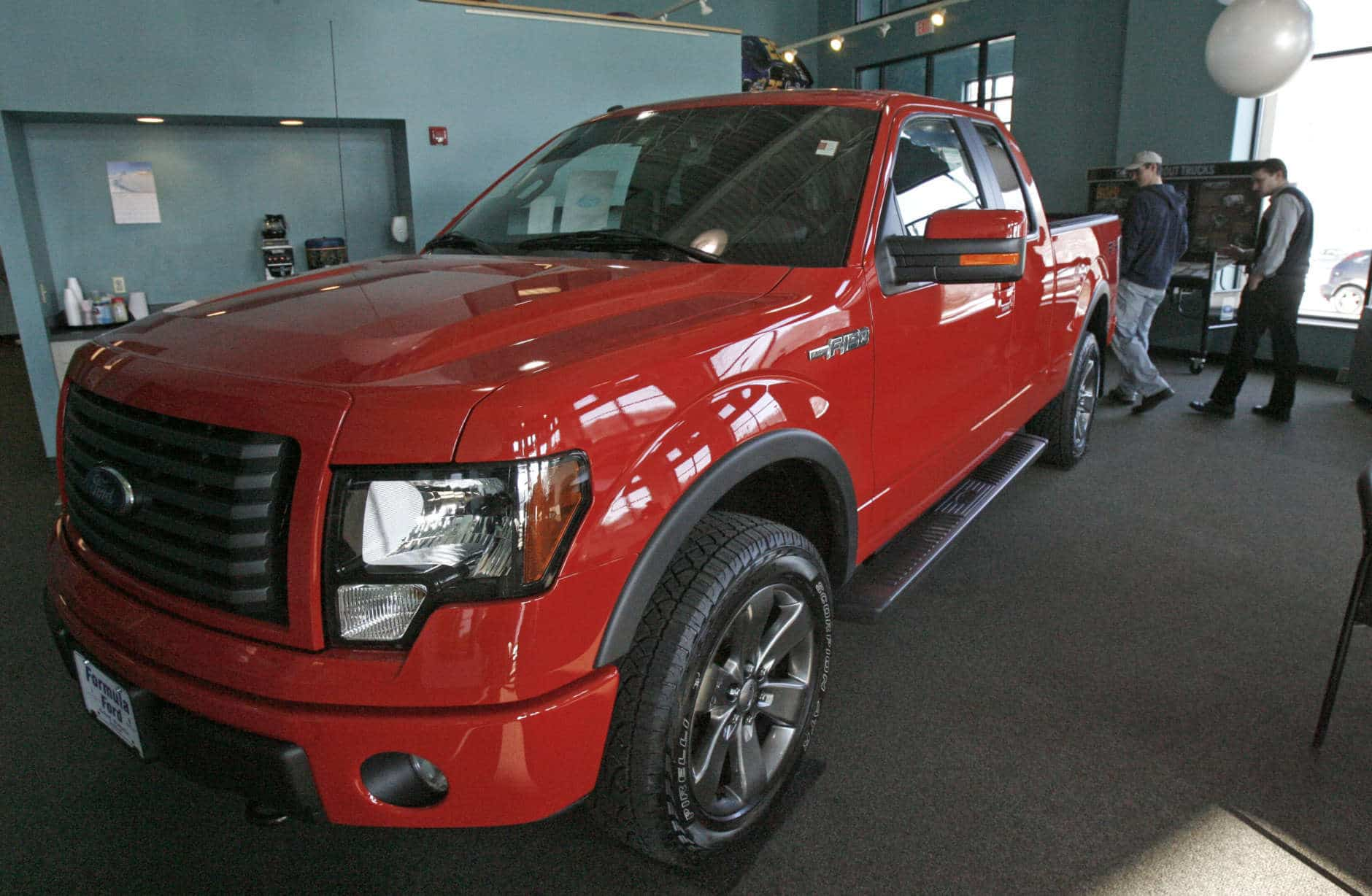 A customer looks over a Ford F-150 in the showroom of Formula Ford on Friday, Jan. 28, 2011 in Montpelier, Vt. Ford earned its biggest profit in more than a decade in 2010 as robust car and truck sales and years of cost cuts paid off for the company. (AP Photo/Toby Talbot)