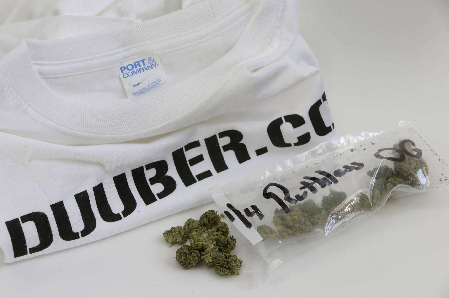 "In this Thursday, Dec. 21, 2017 photo, marijuana and a T-shirt from Duuber.com delivery company are displayed together, in Walpole, Mass. Companies like Duuber.com have been exploiting a provision in state marijuana laws that allows people to exchange up to an ounce of marijuana, so long as it's given away or ""gifted"" without any money exchanged. The T-shirt was $100, but the marijuana was free. (AP Photo/Steven Senne)"