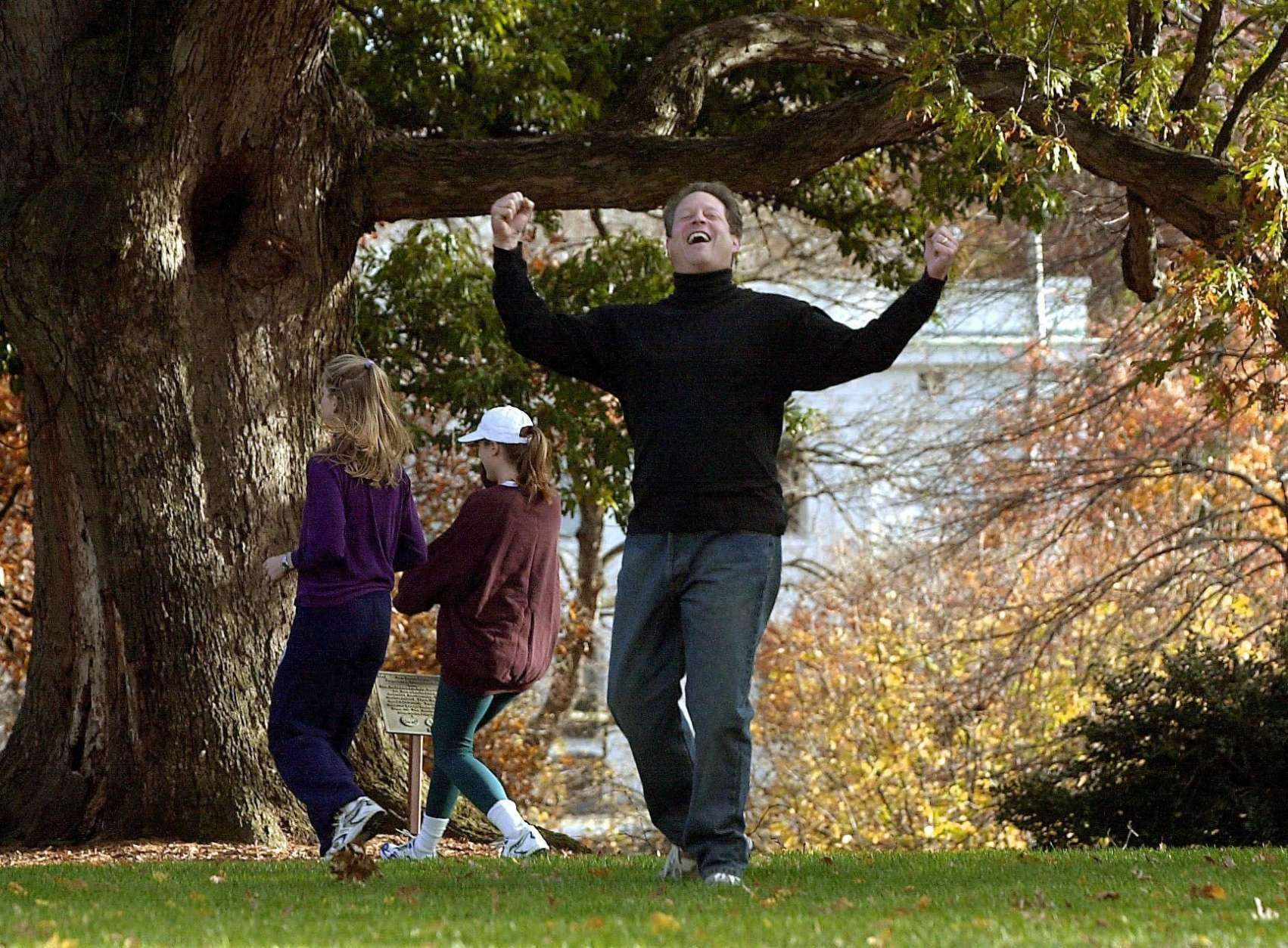 WASHINGTON, :  US Vice President Al Gore (R) celebrates scoring a touchdown as daughters Kristin (C) and Karenna (L) walk away during a touch football game with family members 10 November 2000 at the Vice President's residence in Washington, DC. Gore and Texas Governor George W. Bush are still waiting for results of the Florida vote count to determine the next US president.   AFP PHOTO/Joyce NALTCHAYAN (Photo credit should read JOYCE NALTCHAYAN/AFP/Getty Images)
