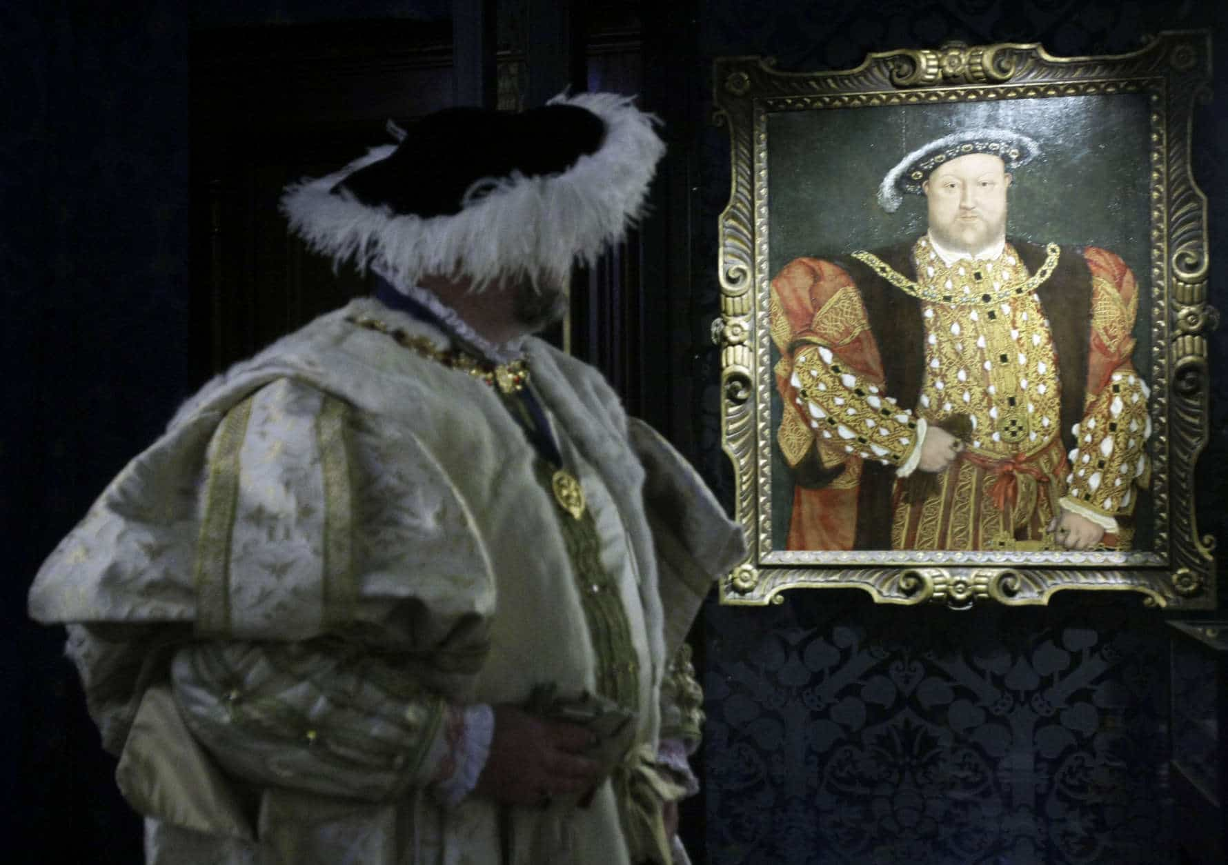 Costumed interpreter Richard Evans, as Britain's King Henry VIII, poses for photographs beside a close copy of a portrait painted during Henry's reign by the German artist Hans Holbein, at Hampton Court Palace, on the outskirts of London, Thursday, April 9, 2009.  The original painting did not survive, with this copy painting being made around 1540 by an artist in the circle of Hans Holbein.  During 2009, King Henry VIII's most famous royal residence plays host to 'Henry VIII: heads and hearts' a year-long programme of events and celebratory activities to mark the Tudor monarch's accession to the throne.  (AP Photo/Matt Dunham)
