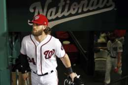 FILE - In this Oct. 12, 2017, file photo, Washington Nationals right fielder Bryce Harper (34) walks in the dugout before Game 5 of baseball's National League Division Series against the Chicago Cubs, at Nationals Park in Washington. There will be one very important question hovering over Harper and the Nationals throughout spring training and the entire 2018 season: Will this be his last year with the club? (AP Photo/Alex Brandon, File)