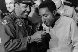 In this handout from the U.S. Air Force, Col. Fred V. Cherry, right, of Portsmouth, Va., relishes his first American cigarette in more than seven years as he gets a light from Lt. Col. James Warren at Gia Lam Airport in Hanoi, North Vietnam, Feb. 13, 1973. Col. Cherry was one of 116 POWs released in Operation Homecoming. Lt. Col. Warren is the navigator of the C-141 transport, the first to fly to Hanoi for the returnees. (AP Photo/USAF)