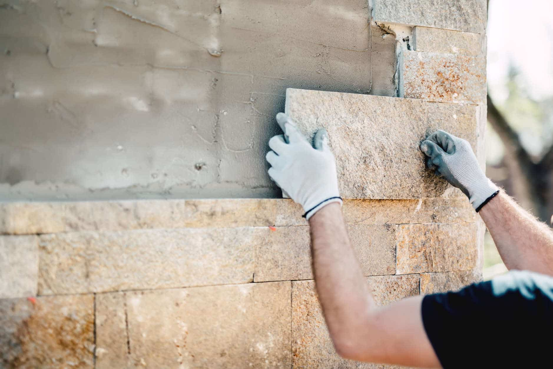 Construction worker installing stone on architectural facade of new building. details of construction industry