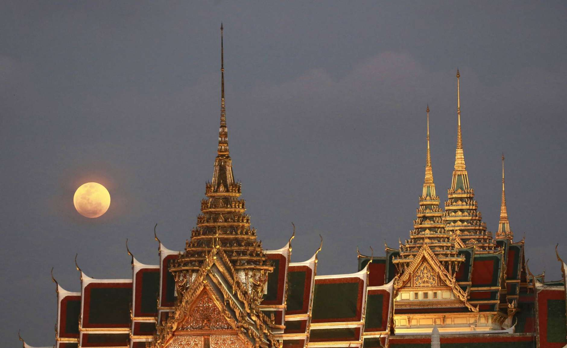 In this Jan. 31, 2018 file photo,  a full moon rises behind the Grand Palace in Bangkok, Thailand. The moon is putting on a rare cosmic show. It's the first time in 35 years a blue moon has synced up with a supermoon and a total lunar eclipse. (AP Photo/Sakchai Lalit)