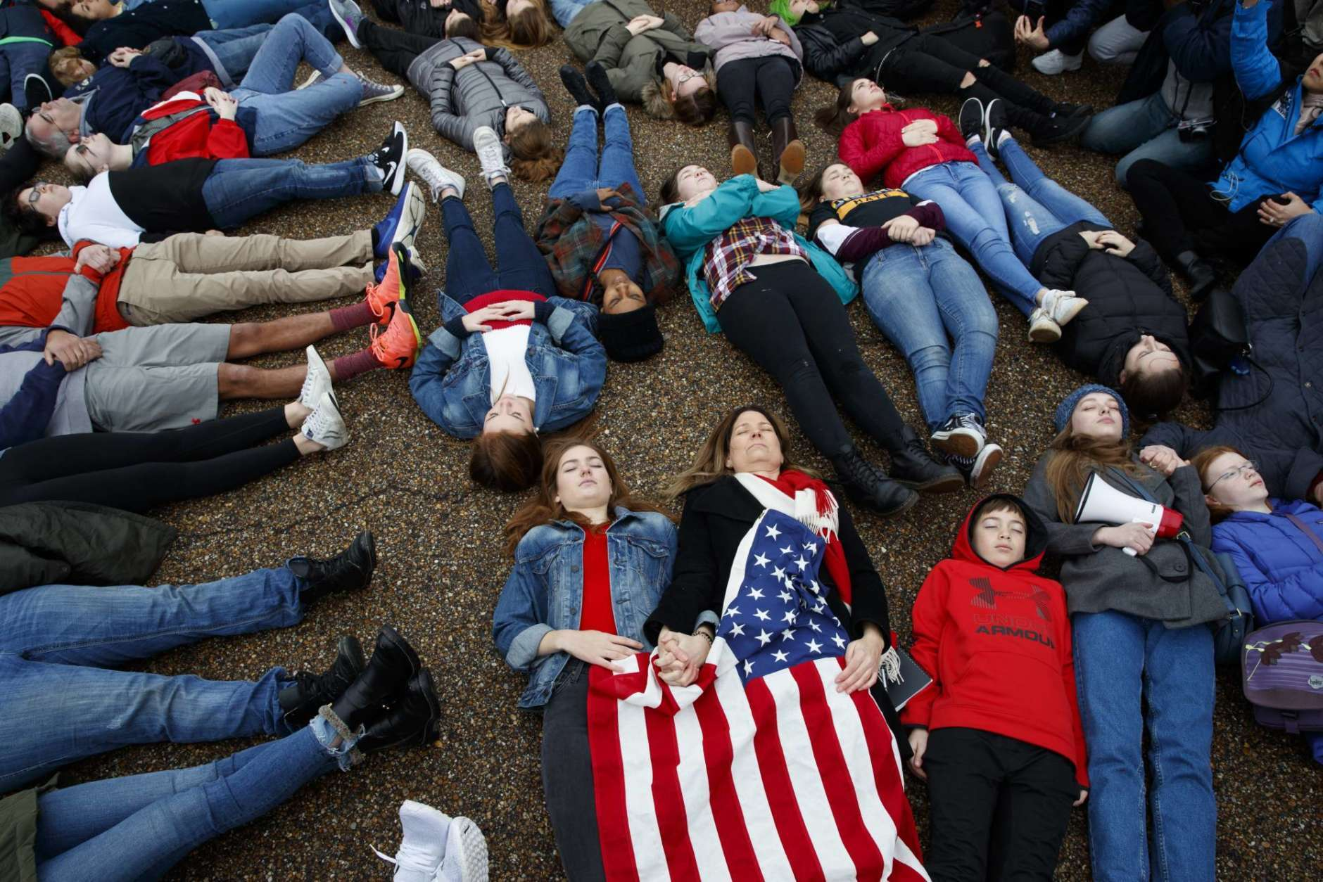 """Abby Spangler and her daughter Eleanor Spangler Neuchterlein, 16, hold hands as they participate in a """"lie-in"""" during a protest in favor of gun control reform in front of the White House, Monday, Feb. 19, 2018, in Washington. (AP Photo/Evan Vucci)"""