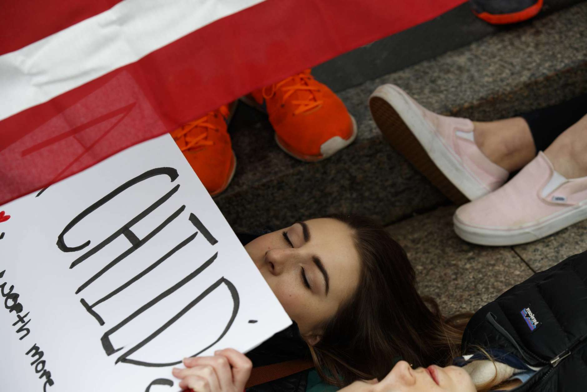 """Anna Hurley, 15, of Washington, top, and other demonstrators participate in a """"lie-in"""" during a protest in favor of gun control reform in front of the White House, Monday, Feb. 19, 2018, in Washington. (AP Photo/Evan Vucci)"""