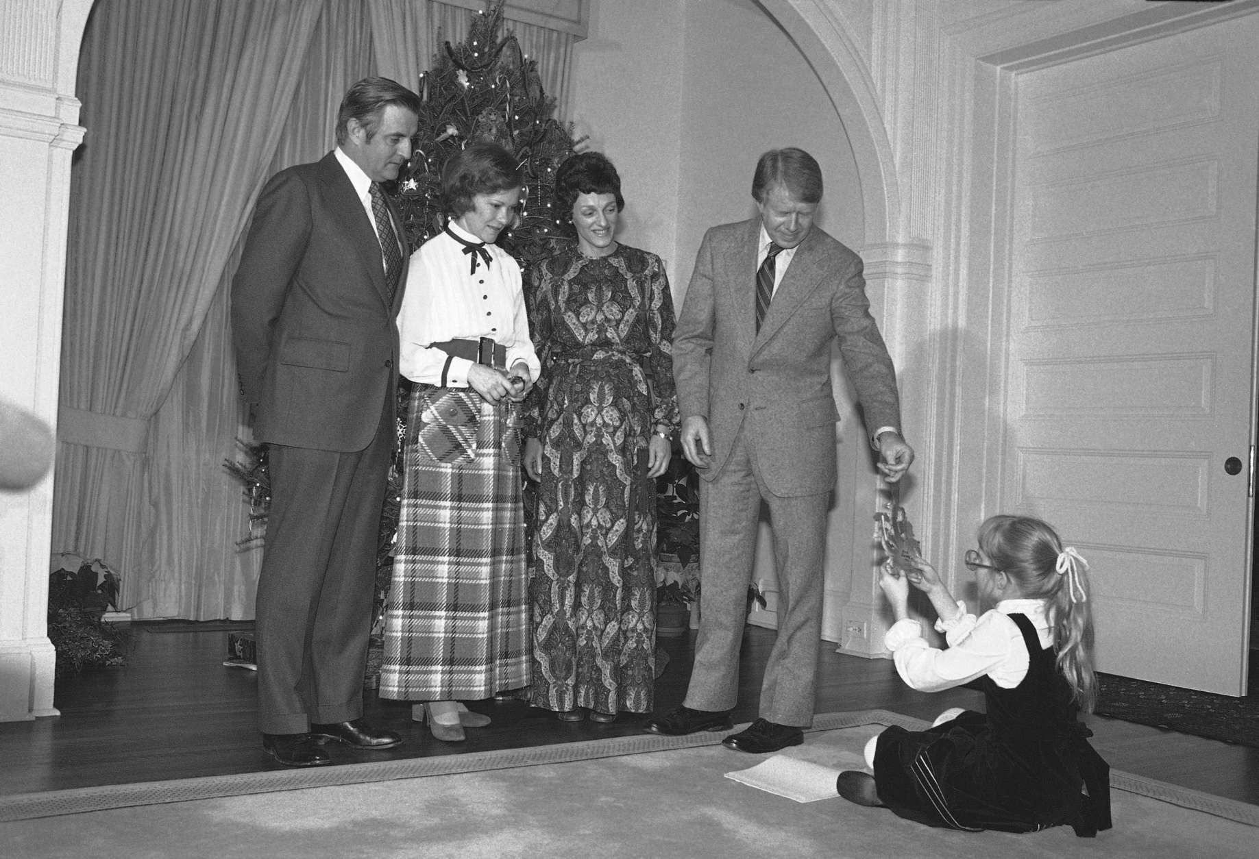 President Jimmy Carter reaches for an ornament from daughter Amy as he poses with Vice President Walter Mondale, left, First Lady Rosalynn Carter, second from left, and Joan Mondale in front of the Mondale's Christmas tree at the Vice President's residence in Washington on Sunday, Dec. 18, 1977. The Carters had dinner with the Vice  President and his wife. (AP Photo)