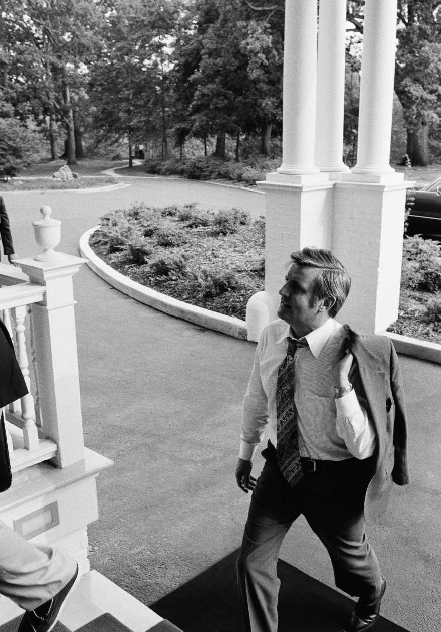 """Vice President Walter Mondale, carrying his coat on a hot day in the capital, arrives at his official residence after what he called """"a typical day"""" at his offices in the White House and in the Executive Office Building next door, Monday, July 19, 1977 in Washington. (AP Photo)"""