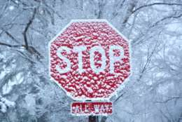 FILE — A stop sign is cloaked in light snow in February 2018. (WTOP/Dave Dildine)