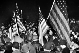 FILE - In this Feb. 12, 1937 file photo, strikers at the General Motors Fisher body plant in Flint, Mich., wave U.S. flags during the Great Depression. At its peak in the early 1970s, GM employed 80,000 people in Flint who cashed paychecks strengthened by the United Auto Workers union born in the city. Some 200,000 people lived in the city's limits, alongside sprawling factories, booming commerce, model schools and thriving arts. (AP Photo/File)