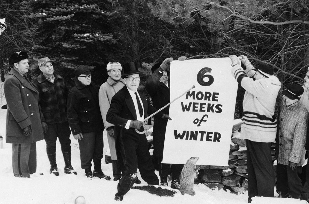 Sam Light, center, president of the Punxsutawney Groundhog Club, points to a sign held by members of the club in Gobbler's Knob, Punxsutawney, Pennsylvania, Jan. 1961.  They posed for the picture a few days before Groundhog Day, Feb. 2, with a stuffed stand-in for Punxsutawney Phil.  (AP Photo)