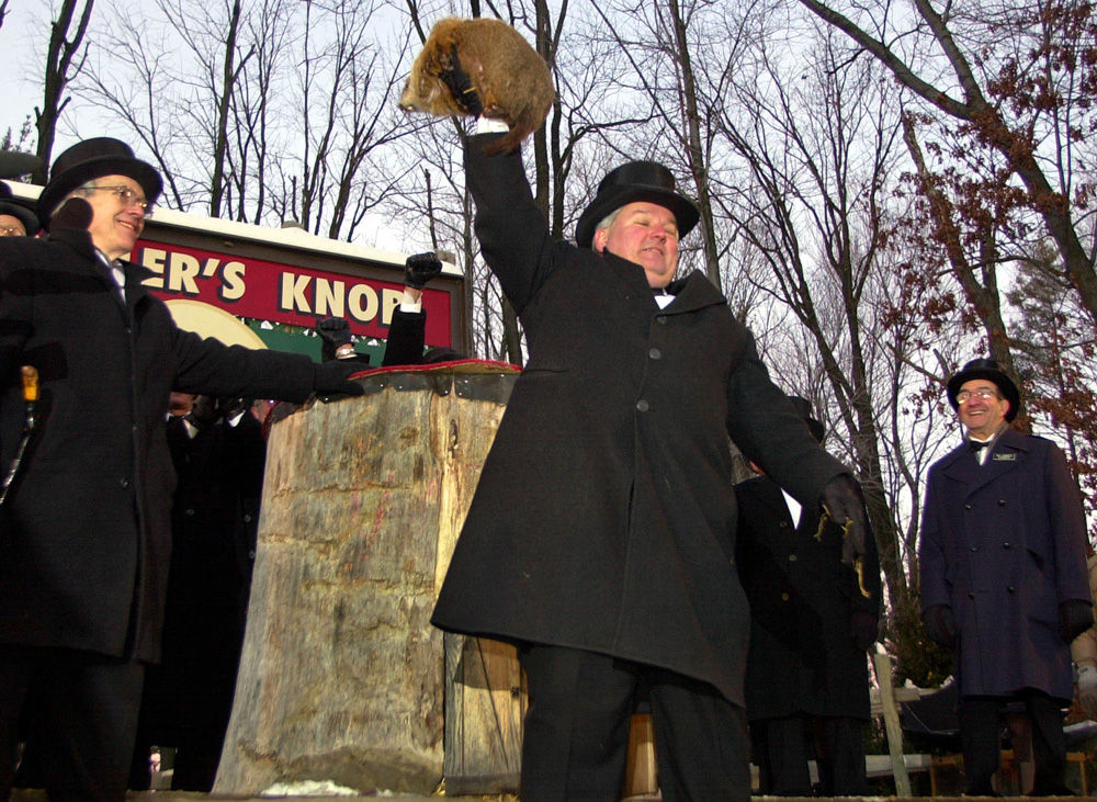 Punxsutawney Phil, the weather prognosticating groundhog from Gobblers Knob in Punxsutawney, Pa., is held high by handler Bill Deeley, center,  after seeing his shadow at 7:27 am Monday, Feb. 2, 2004, and predicting six more weeks of winter. (AP Photo/Gene J. Puskar)
