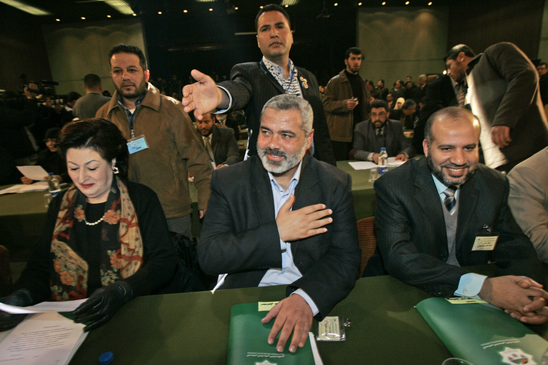Ismail Haniyeh, Hamas' apparent choice for prime minister, center, replys to a greeting of lawmakers inside the Palestinian parliament in Gaza City, Saturday, Feb. 18, 2006. A Hamas-dominated Palestinian parliament was sworn in Saturday, and Palestinian leader Mahmoud Abbas was expected to ask the Islamic militant group in his opening address to accept his moderate policies, including negotiations with Israel. (AP Photo/Alexander Zemlianichenko)