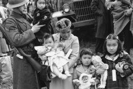 FILE - In this March 30, 1942 file photo, Cpl. George Bushy, left, a member of the military guard which supervised the departure of 237 Japanese people for California, holds the youngest child of Shigeho Kitamoto, center, as she and her children are evacuated from Bainbridge Island, Wash. Throughout American history, during times of war and unrest, authorities have cited various reasons and laws to take children away from their parents. Examples include Native American boarding schools, Japanese internment camps and deportations that happened during the Great Depression. (AP Photo/File)