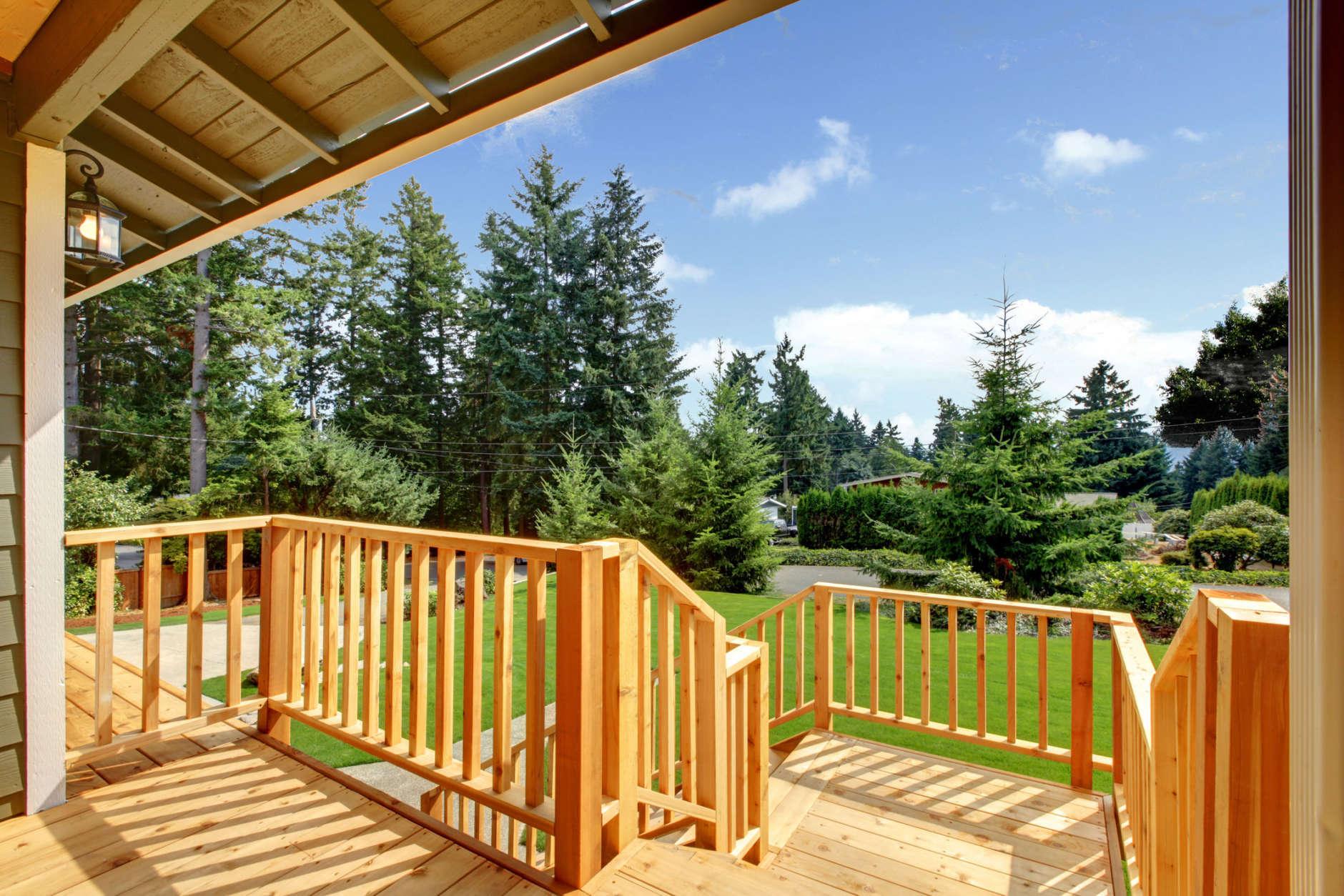 Wooden walkout deck with patio area overlooking backyard. Northwest, USA