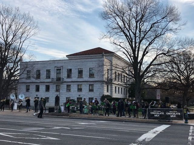 People gather on the side of the marathon route Saturday. (WTOP/Melissa Howell)