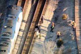 People on the tracks near where an Amtrak train struck a vehicle. (NBC Washington/Brad Freitas)
