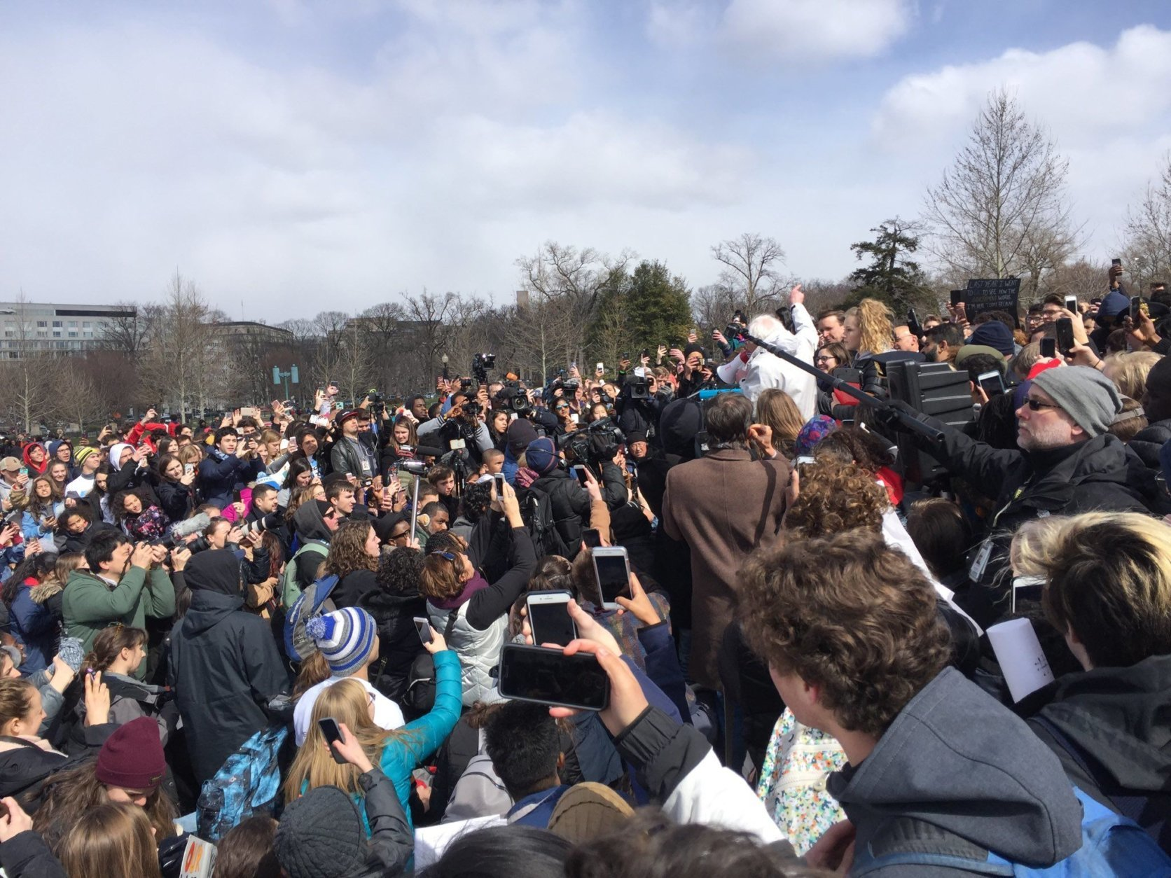 Sen. Bernie Sanders' arrival (center in white) caused an uproar among students  demanding action at the U.S. Capitol. (WTOP/Kristi King)
