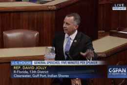 """In this frame grab from video provided by C-SPAN, Rep. David Jolly, R-Fla. holds a container of mosquitoes while speaking of the House floor on Capitol Hill in Washington, Wednesday, Sept. 7, 2016. """"The politics of Zika are garbage right now,"""" the Florida lawmaker said in a short, angry speech condemning Congress for failing to pass legislation providing $1.1 billion to combat the mosquito-borne virus.  (C-SPAN via AP)"""