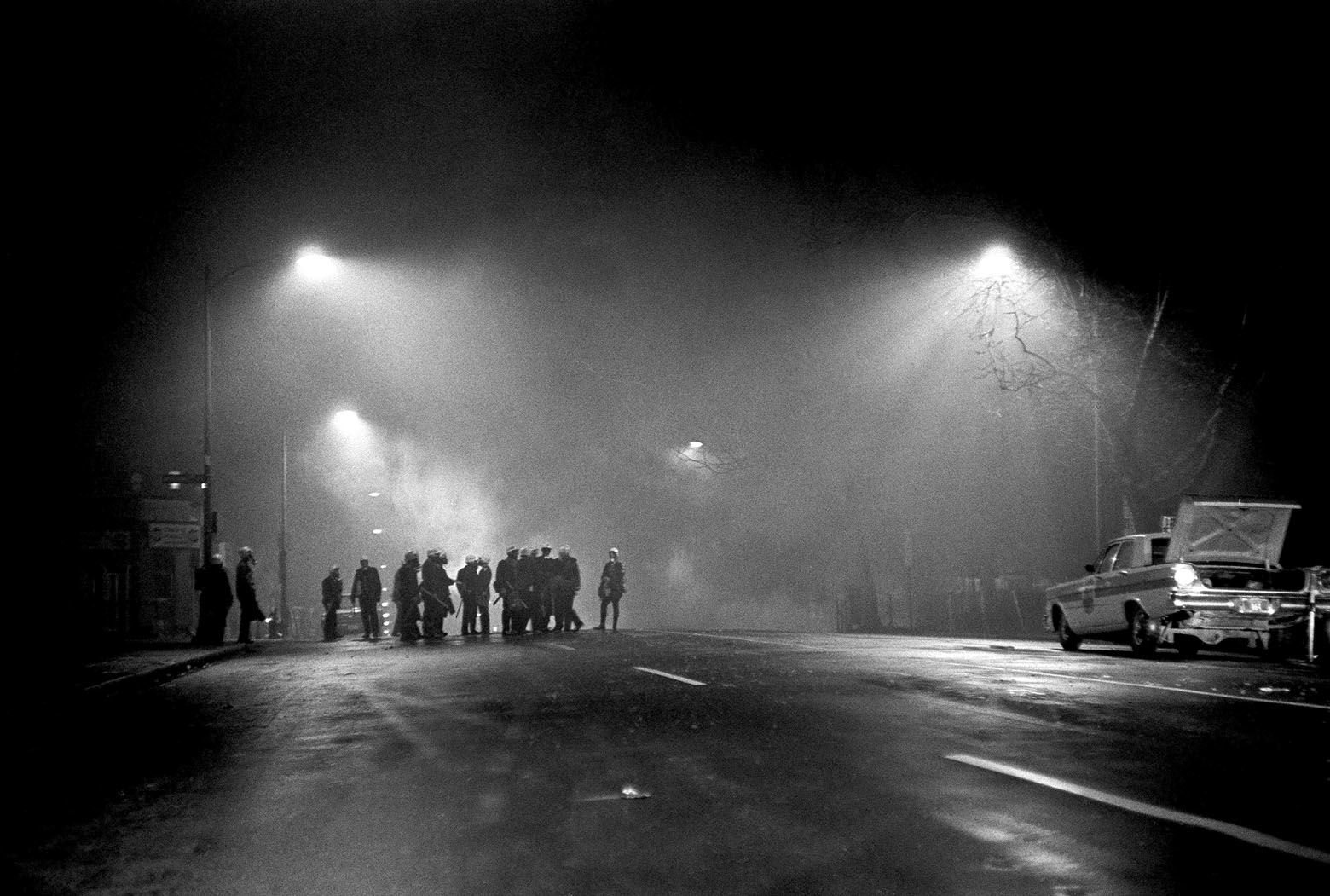 Tear gas, illuminated by street lights, fills the air as police wearing gas masks await possible further trouble in an African American area of northwest Washington on April 5, 1968. Crowds looted and started fires after learning of death of Dr. Martin Luther King Jr. (AP Photo/Charles W. Harrity)