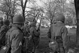 Soldiers of the 3rd Infantry Regiment from Fort Myer, Va., take up posts in Lafayette Park near the White House in background on April 5, 1968. They were part of the Federal troops ordered into the nation's capital by President Lyndon Johnson as looting and burning flared in the downtown area. (AP Photo/Henry Burroughs)