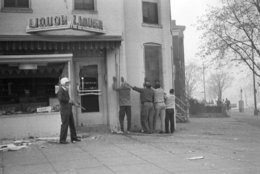 A helmeted policeman, armed with a shotgun, lines up four men after the window of a liquor store was smashed in northeast Washington on April 5, 1968 during renewed looting and burning. (AP Photo/Dozier Mobley)