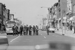 Police, equipment with gas masks and canisters of tear gas, block a downtown Washington street as looting and arson spread on April 5, 1968. Several stores near this blockaded area were set afire. (AP Photo/Bob Schutz)