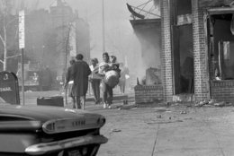 Women carry armloads of clothing and other articles as they walk past a northwest Washington area at 7th and U Streets, April 5, 1968. The area, still dimmed by smoke from burning buildings, was one of the hardest hit as looting and arson flared in the nation's capital. (AP Photo/Bob Schutz)