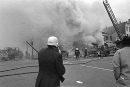 Police stand guard as firemen battle fires in the troubled area of the Capital, Washington, April 6, 1968. The trouble erupted following a night when a curfew was imposed and most burning and looting had subsided. (AP Photo/Charles Tasnadi)