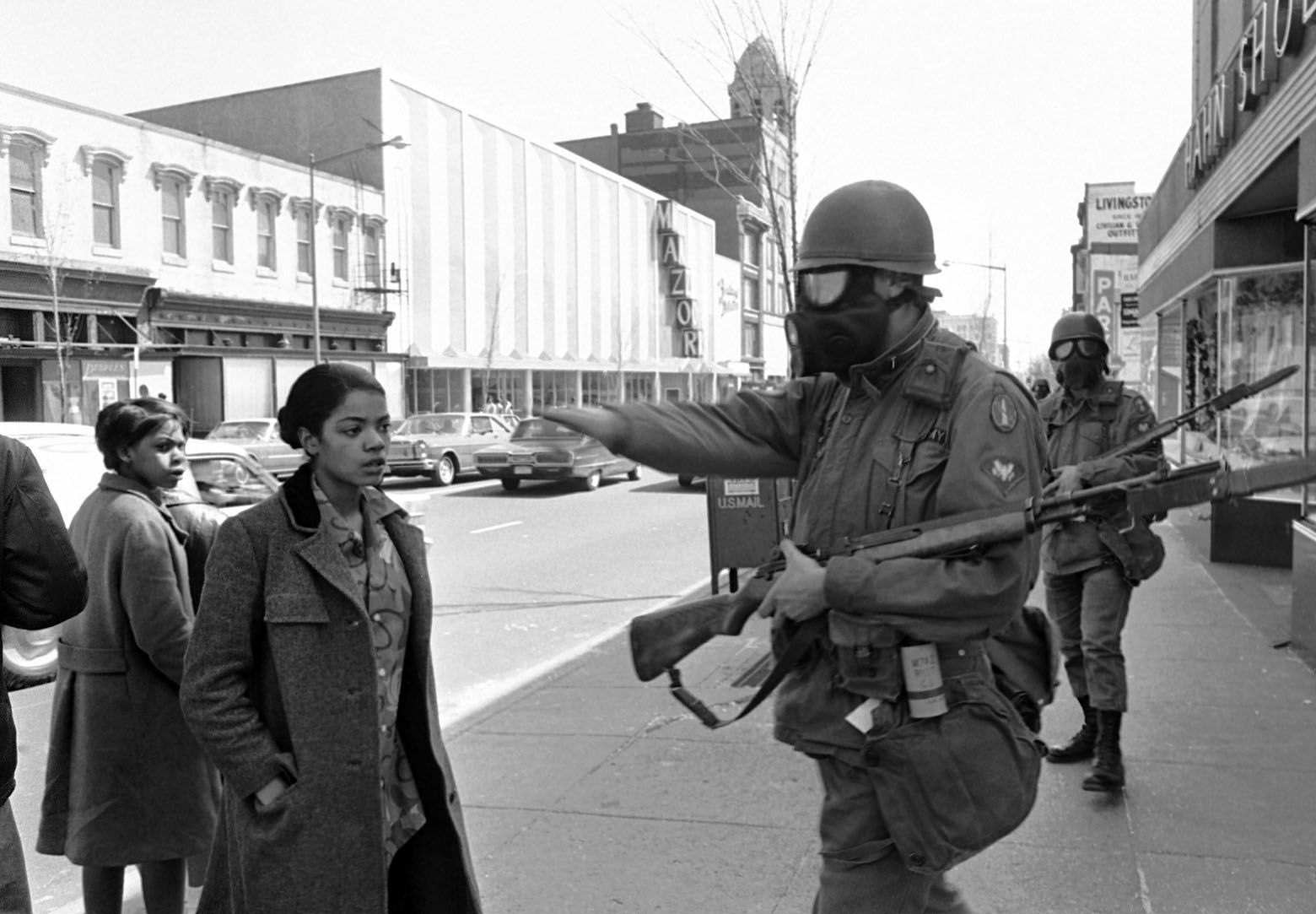 A pedestrian is waved away from a barred area by a gas-masked Army trooper guarding an area near 7th and K Streets, in northwest Washington on April 6, 1968. Another trooper is behind him. Their bayoneted rifles are sheathed. (AP Photo/Bob Schutz)