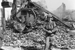 An Army trooper stands guard at the corner of 8th and H Streets in northeast Washington on April 6, 1968 before a pile of rubble which once was a jewelry stores. A coiled fire hose is in the street. Shells of fire-gutted, building are in the background. (AP Photo/Bob Schutz)